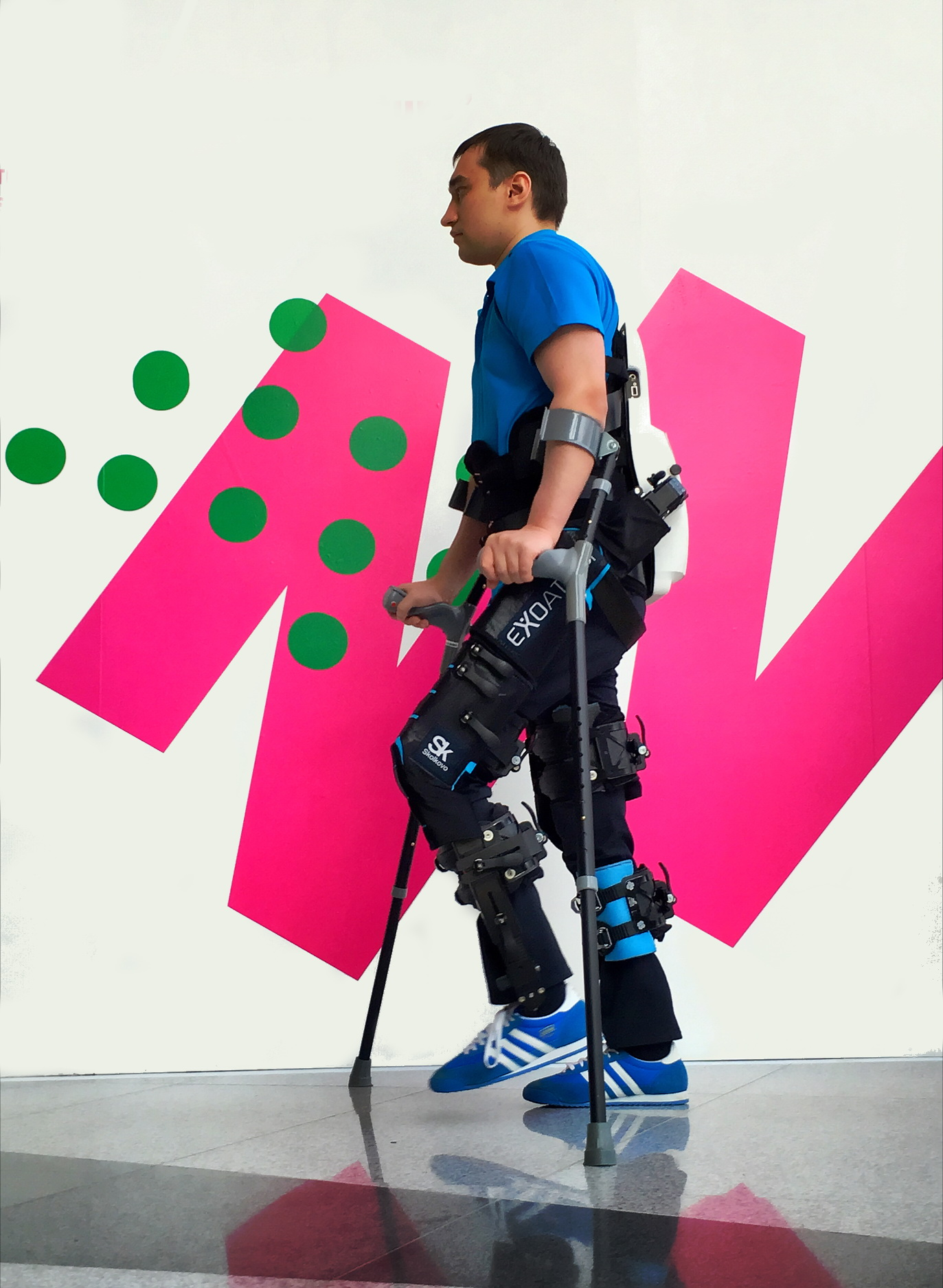 Figure 3. The ExoAtlet. This is an electrically actuated exoskeleton that assists patients suffering from leg paralysis. The ExoAtlet allows to set the stepping parameters and enacts several bipedal states, such as standing, walking on different surfaces and stepping over obstacles. Reproduced with permission from Ekaterina Bereziy, exoatlet.ru.